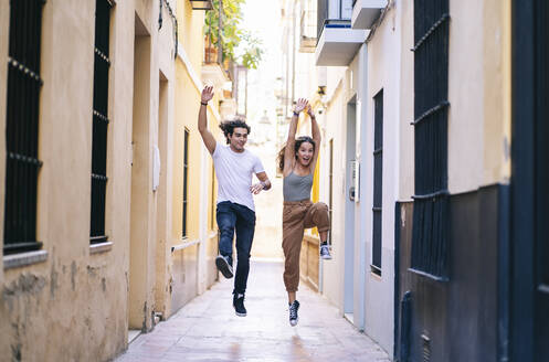 Full length of carefree young couple jumping on narrow street at Santa Cruz, Seville, Spain - DGOF00879