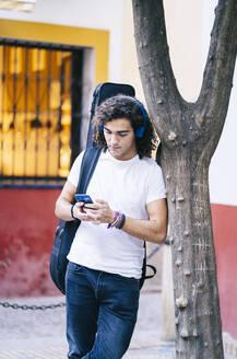 Young man using mobile phone while carrying guitar bag, Santa Cruz, Seville, Spain - DGOF00882