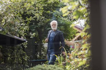 Senior man smoking cigarette in the garden - JOSEF00254