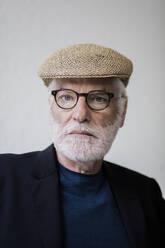 Portrait of bearded senior man with white hair wearing cap - JOSEF00263