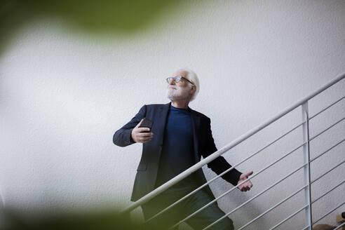 Senior man taking selfie with smartphone while posing on stairs - JOSEF00269