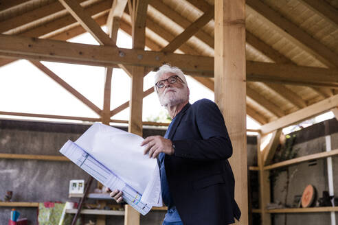 Senior man with construction plan standing in a shelter looking up - JOSEF00272
