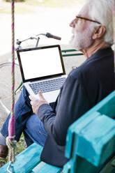Senior man sitting outdoors using laptop - JOSEF00275