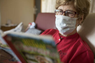 Senior woman reading roman at home and wearing protective mask - JATF01179