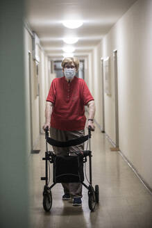 Senior woman wearing mask and walking with wheeled walker in corridor of retirement home - JATF01182
