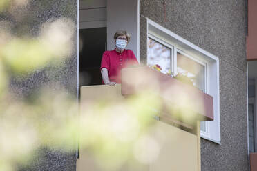 Senior woman wearing mask on balcony, retirement home - JATF01185