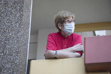 Senior woman wearing mask on balcony, retirement home - JATF01188