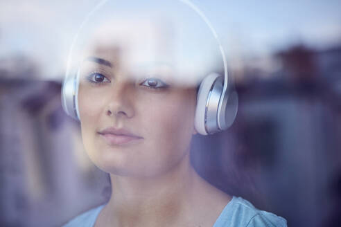 Portrait of young woman listening music with headphones looking out of window - JHAF00116