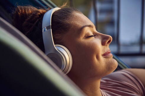 Smiling young woman lying on hammock on balcony listening music with headphones - JHAF00128