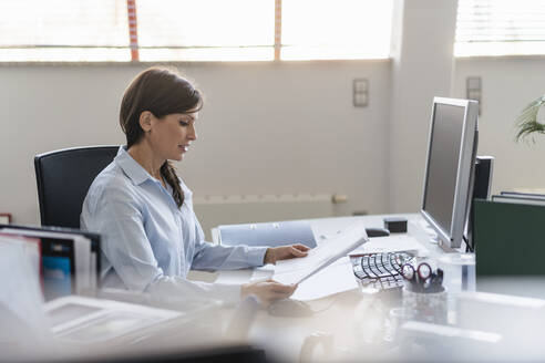 Businesswoman working at desk in office - DIGF09688