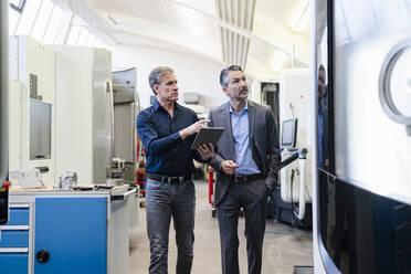 Businessmen in factory, having a meeting, using digital tablet - DIGF09835