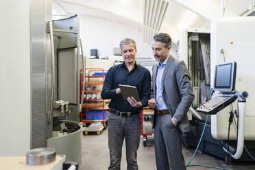 Businessmen in factory, having a meeting, using digital tablet - DIGF09838