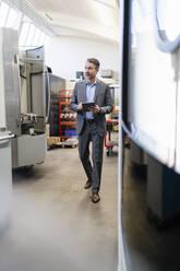 Mature businessman walking on production floor of factory, using digital tablet - DIGF09844