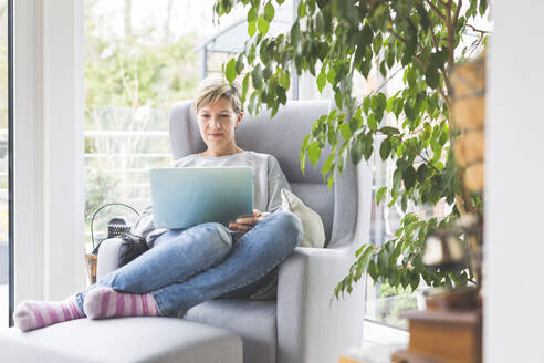 Mature woman working from home, using laptop, sitting in armchair - ASCF01249