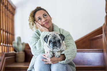 Woman sitting on stairs, with pug on her lap - SIPF02155