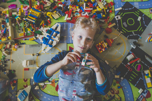 High angle portrait of boy playing with toy blocks at home - IHF00331