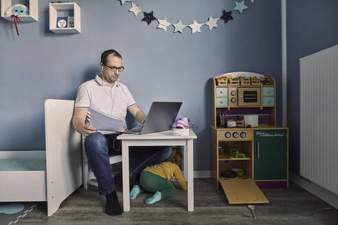 Man working and using laptop in children's room with simultaneous childcare - SEBF00289