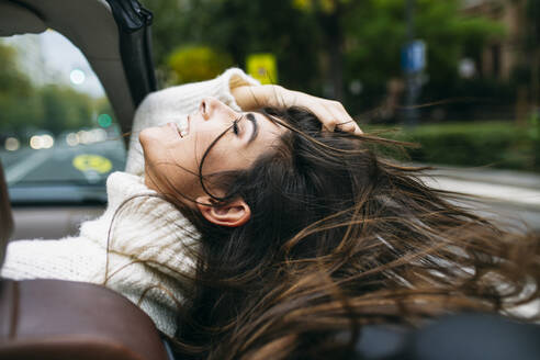 Happy woman with tousled hair enjoying wind in convertible car - ABZF03093