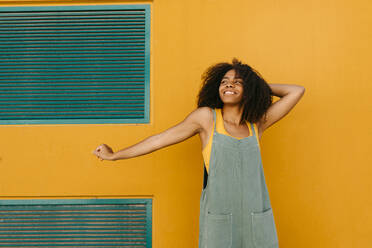 Portrait of happy young woman wearing overalls in front of yellow wall - TCEF00474