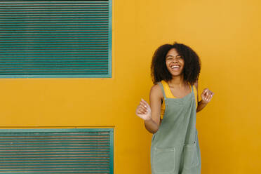 Portrait of happy young woman wearing overalls in front of yellow wall - TCEF00477