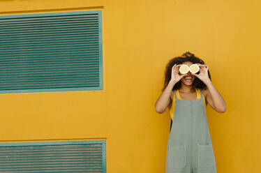 Happy young woman wearing overalls in front of yellow covering her eyes with lemons - TCEF00480