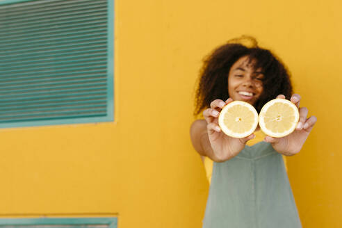 Happy young woman wearing overalls in front of yellow wall holding lemons - TCEF00483