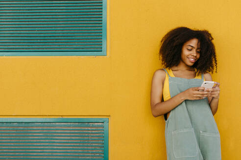 Smiling young woman wearing overalls in front of yellow wall using smartphone - TCEF00486