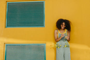 Portrait of happy young woman wearing overalls holding flowers in front of yellow wall - TCEF00492