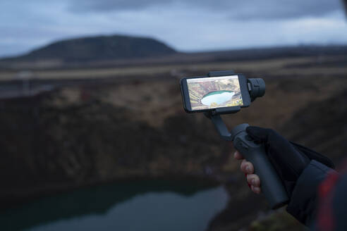Iceland, Hand of person photographing crater lake - DAMF00359