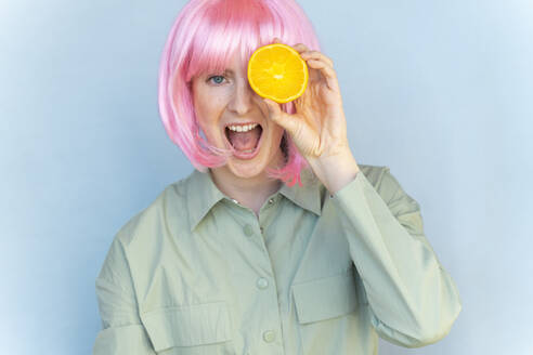 Portrait of carefree young woman wearing pink wig holding an orange - AFVF06083