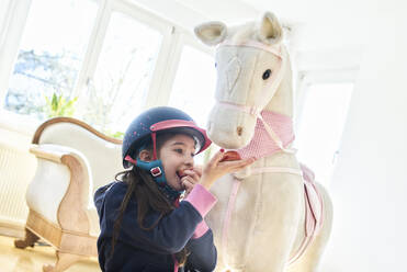 Girl feeding her toy horse at home - DIKF00464