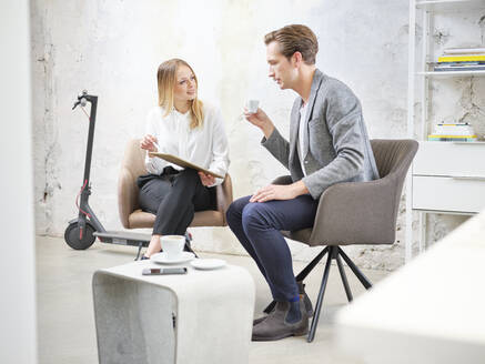 Businessman and businesswoman with tablet having a meeting in modern office - CVF01605
