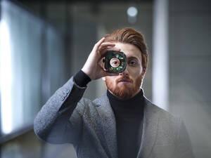 Portrait of businessman looking through an object in modern office - CVF01617