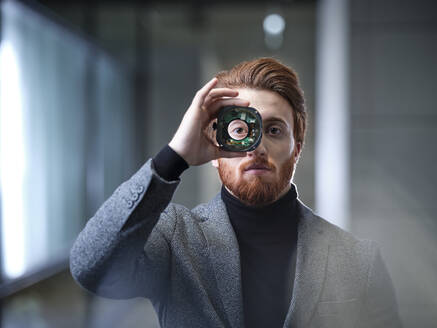 Portrait of businessman looking through an object in modern office - CVF01617
