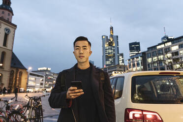 Man using smartphone beside a taxi at evening on the street - AHSF02258