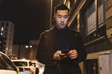 Man using smartphone in the city at night - AHSF02270