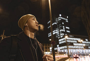 Stylish man with yellow hat and earphones smoking a cigarette in the city at night - AHSF02273