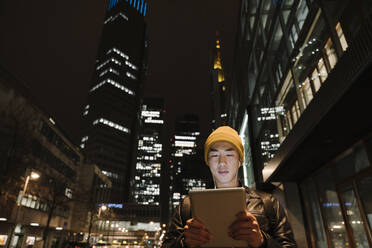 Man using tablet in the city at night - AHSF02279