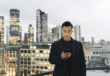 Man using smartphone in the city at dusk - AHSF02282