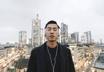 Man with headphones in front of urban skyline, Frankfurt, Germany - AHSF02285