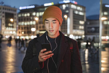 Man with earphones using smartphone in the city at night - AHSF02288