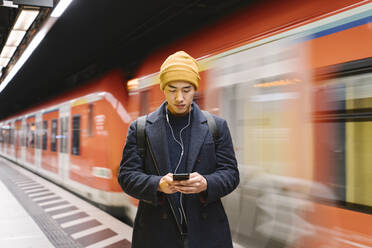 Stylish man with smartphone and earphones in metro station - AHSF02291
