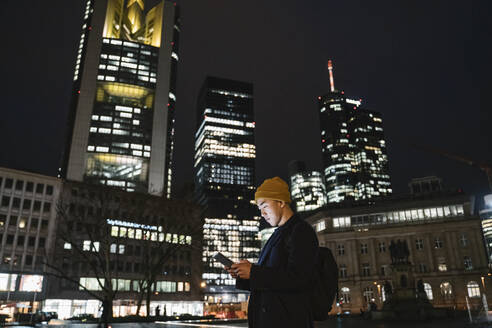 Man using tablet in the city at night - AHSF02294