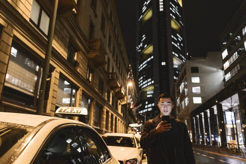 Man using smartphone while walking in the city at night - AHSF02297