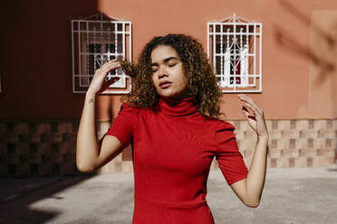 Young woman wearing red dress enjoying sunlight with closed eyes - TCEF00509