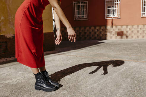Young woman wearing red dress and black boots, playing with her shadow on the floor - TCEF00515
