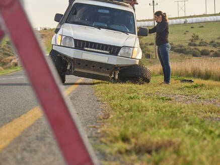 Safety triangle warning of a car accident on the side of the road with woman on the phone, South Africa - VEGF01916