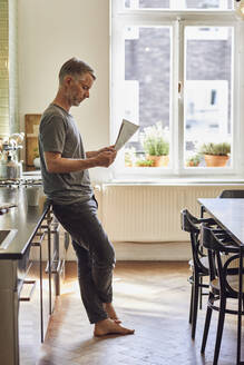 Mature man reading newspaper in kitchen at home - MCF00684
