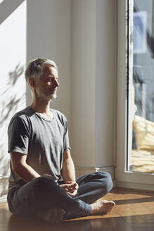 Mature man sitting on the floor at home meditating - MCF00690