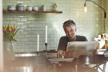 Smiling mature man sitting in kitchen reading newspaper - MCF00702